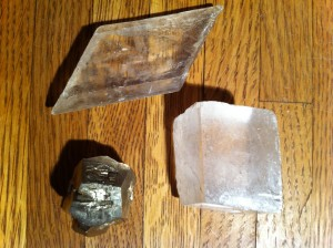 Fig. 1.  Examples of three different crystals that are relatively common gypsum, calcite and pyrite (clockwise from top left). The calcite crystal is approximately an inch wide.